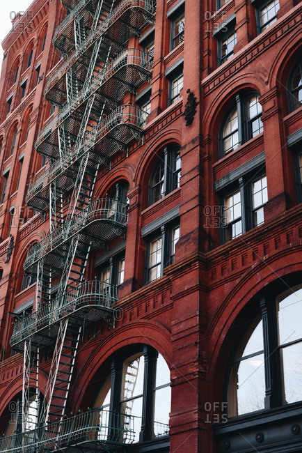 Red city building exterior with fire escape in NYC
