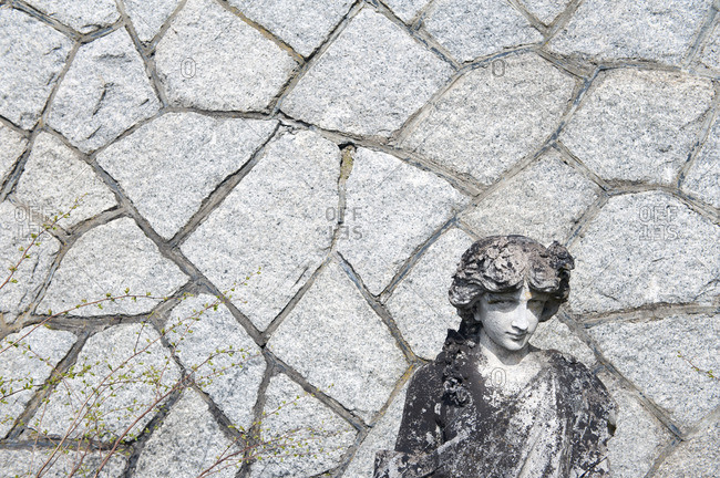 Weathered statue against stone wall