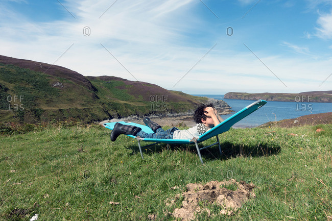 Young boy holding his hands over his face on a folding chair overlooking the north sea