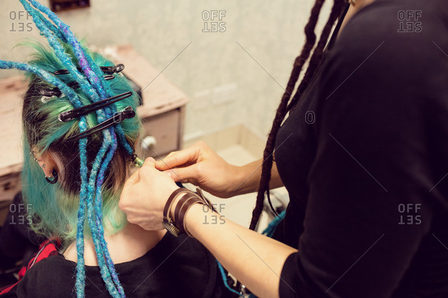Beautician styling clients hair in dreadlocks shop