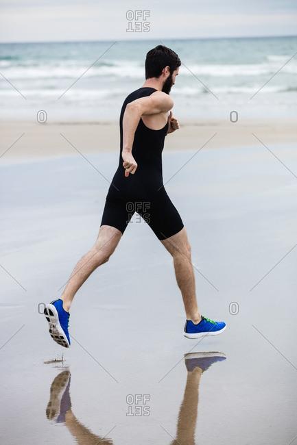 Handsome Man running on the beach
