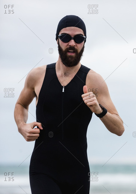 Athlete in swimming goggles running on the beach