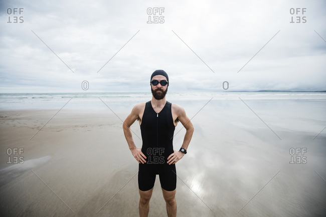 Athlete in swimming goggles standing with hand on hip at beach