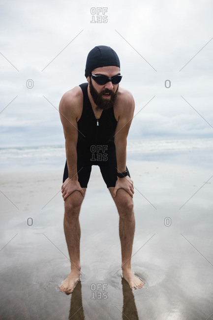 Tired man taking a break while jogging on beach
