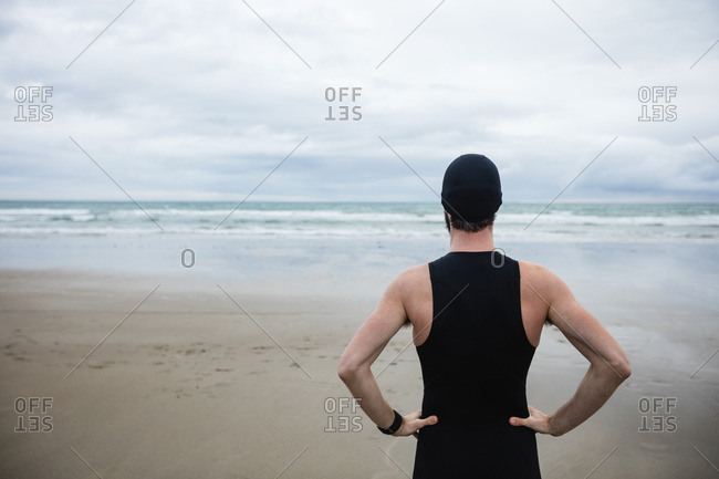 Athlete in swimming costume standing with hand on hip at beach