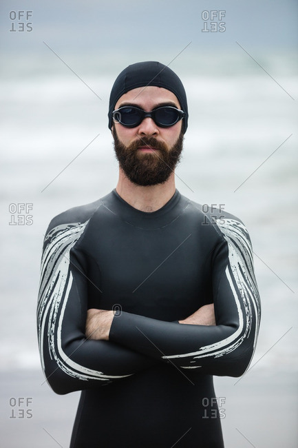 Athlete in wet suit standing with his arms crossed on beach