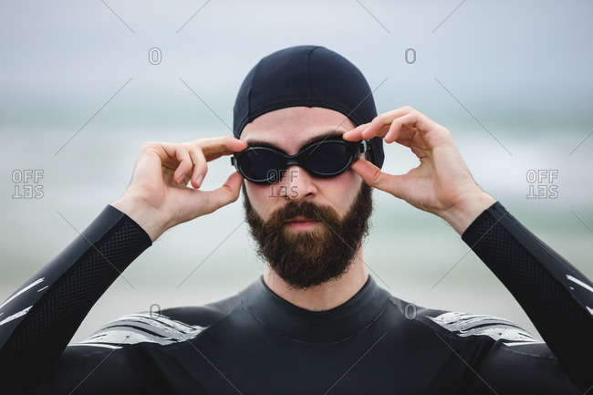 Athlete in wet suit wearing swimming goggles on beach