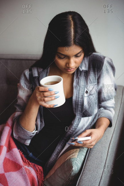 Woman using mobile phone while holding cup of coffee in living room at home
