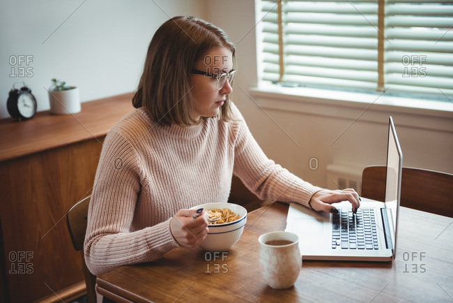 Woman using laptop while having breakfast in living room at home