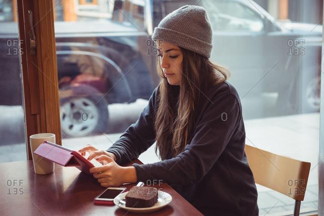 Woman in winter clothing using digital tablet in restaurant