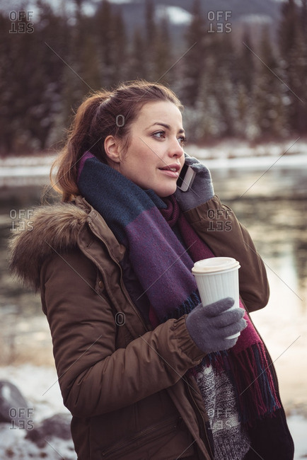 Woman standing on river bank and using mobile phone in winter