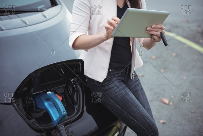 Mid section of woman using digital tablet while charging electric car on street