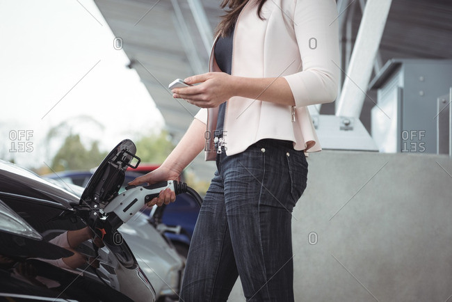 Mid section of woman using mobile phone while charging electric car vehicle charging station