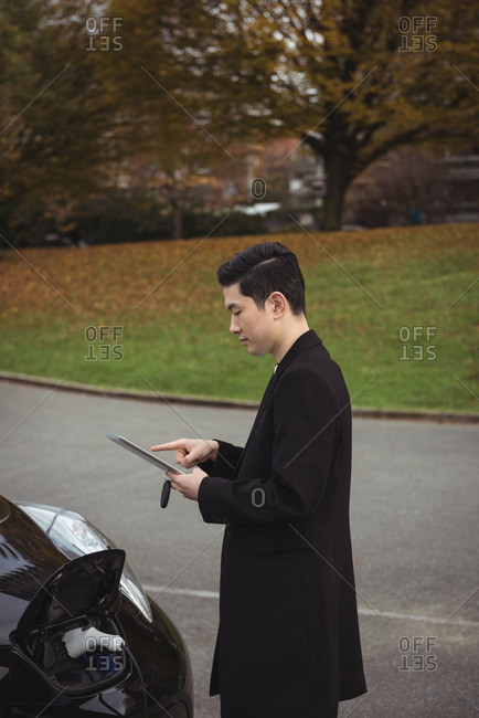 Man using digital tablet while charging electric car at electric vehicle charging station