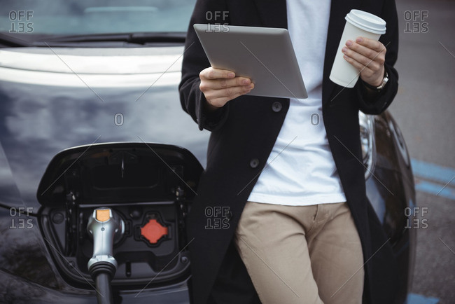 Mid section of man using digital tablet while charging car at electric vehicle charging station