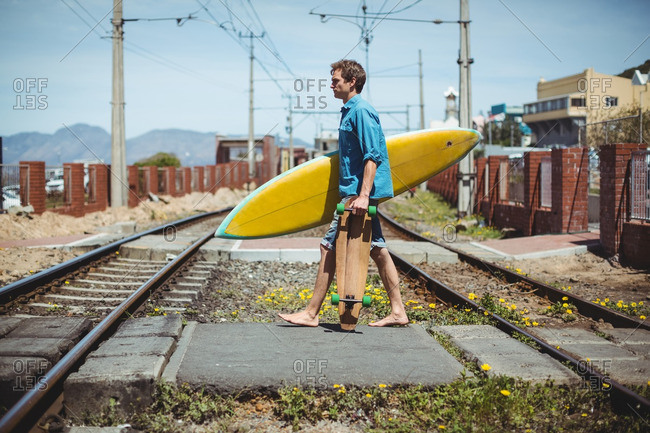 Man carrying skateboard and surfboard crossing railway track