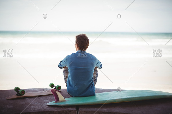 Rear view of man with skateboard and surfboard sitting on beach