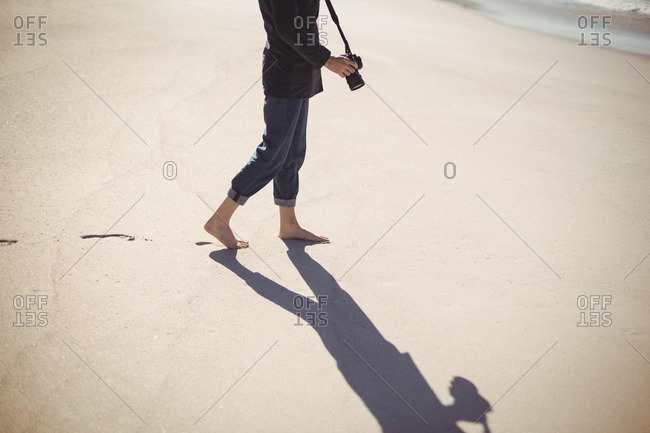Woman with digital camera walking on the beach