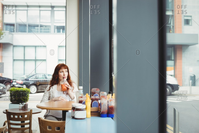 Pregnant businesswoman having fruit juice in office cafeteria