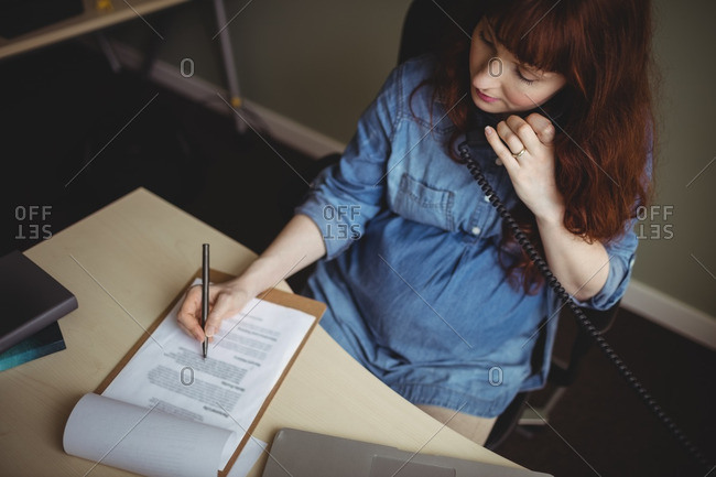 Pregnant businesswoman talking on telephone while working in office