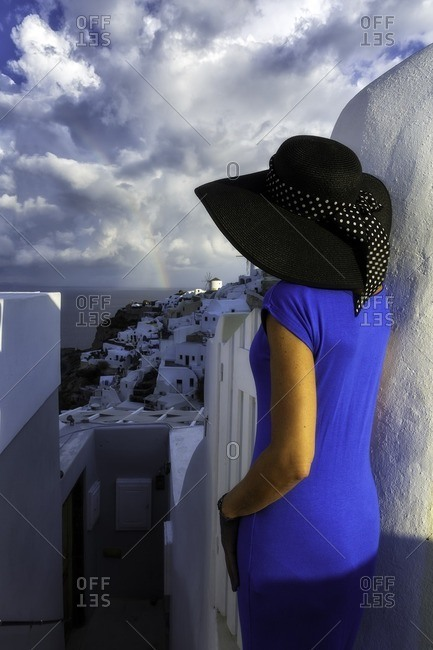 Panoramic view of Santorini island from old church ruins in Oia with a model in blue dress