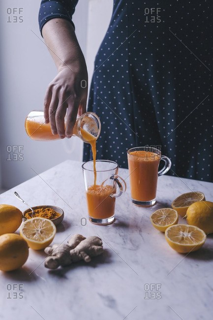 Woman pouring orange, lemon and carrot juice with turmeric and ginger into a glass