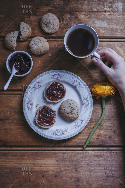 Woman holding a cup of black tea and eating bread buns with raspberry jam