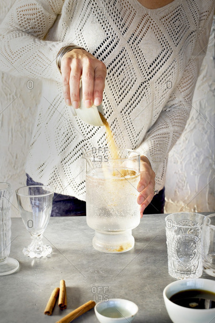 A Women is pouring sugar into Soda Water in glassware. Photographed on dark gray background.