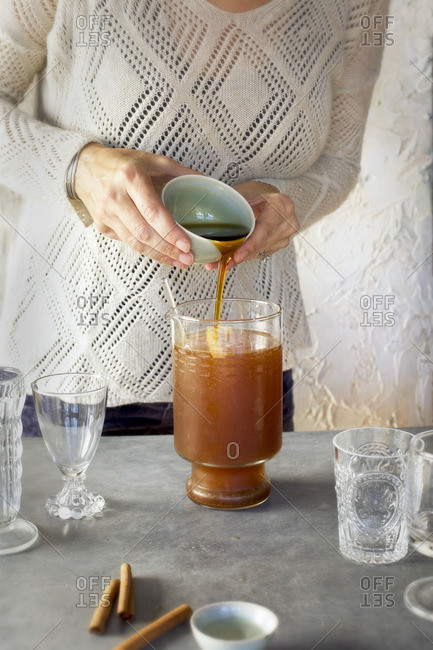 A Women is pouring maple syrup into Almond Lime Italian Soda in glassware. Photographed on dark gray background.