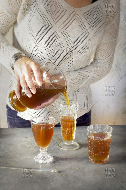 A Women is pouring Almond Lime Italian Soda into glassware. Photographed on dark gray background.