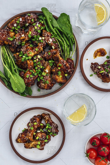 Oven-baked chicken wings with a sticky sauce and sesame seeds served with herbs on one large plate and two small plates accompanied by soda with lemon and cherry tomatoes.