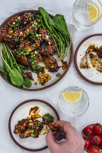 Oven-baked chicken wings with a sticky sauce and sesame seeds served with herbs on one large plate and two small plates accompanied by soda with lemon and cherry tomatoes. A man is grabbing one chicken wing.