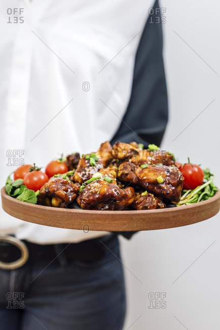 A woman with a white and grey shirt and grey pants serving chicken wings, herbs and tomatoes on a plate.