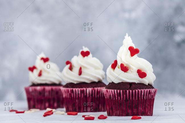 Red velvet cupcakes with buttercream frosting and decorated with heart shaped sprinkles.