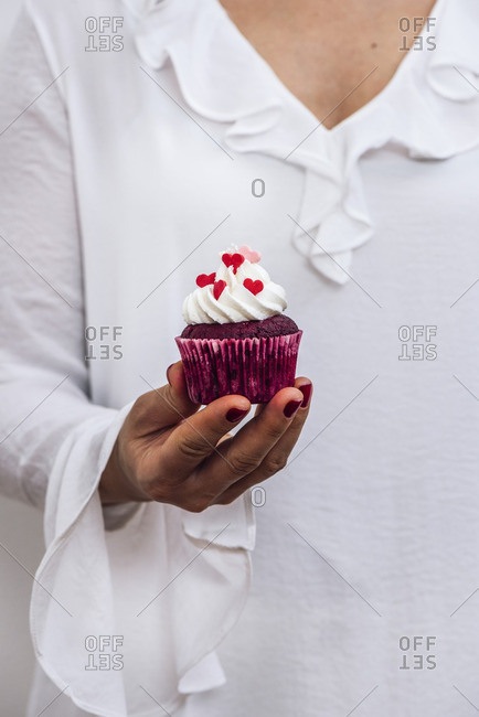 A woman with a white dress is holding a red velvet cupcake in her hand photographed from front view.