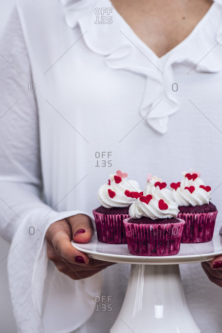 A woman with a white dress holding a cake stand full of red velvet cupcakes photographed from front view.