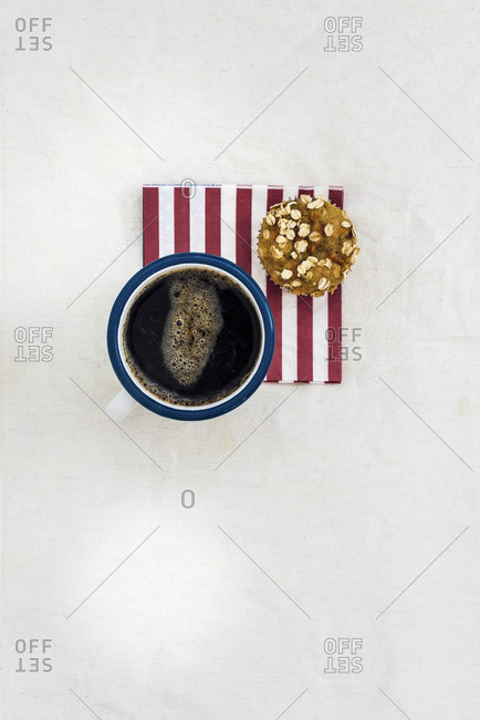 A mug of coffee and a carrot muffin on a red striped napkin photographed from top view.