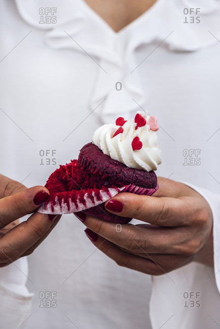 A woman with a white dress is holding a red velvet cupcake in her hand, removing the liner photographed from front view.