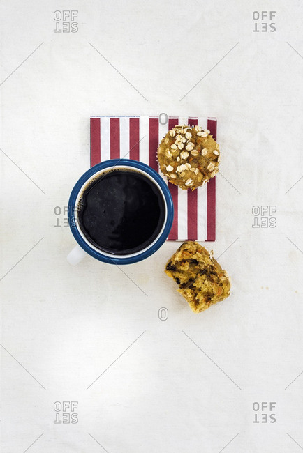 A mug of coffee and a carrot muffin on a red striped napkin photographed from top view. Half of a muffin is on the side.