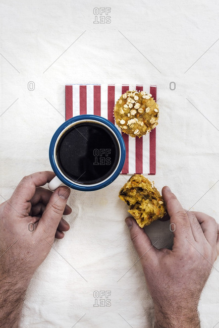 A man having carrot muffins with coffee on a red striped napkin photographed from top view.