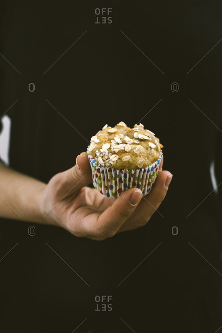 A woman with black dress holding a carrot muffin photographed from front view.