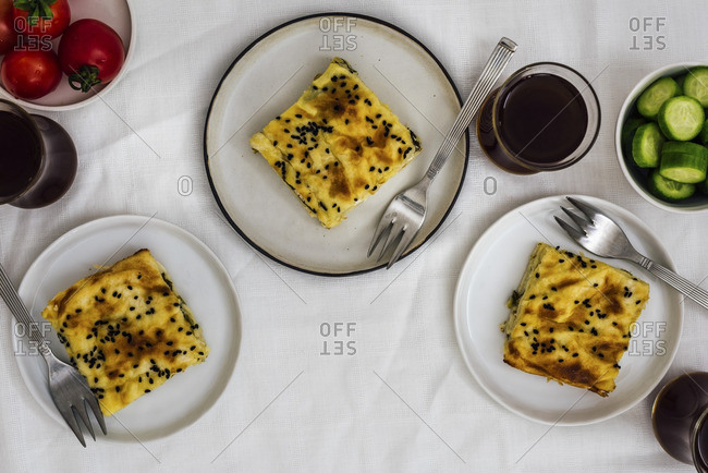Phyllo pastry stuffed with cheese and herbs and cut into squares served on three small plates with forks on the side. Tomatoes, cucumbers and Turkish tea accompany them.