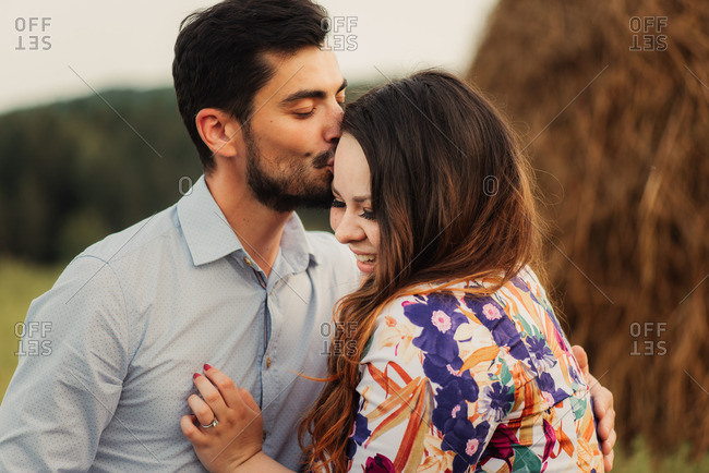 Man kissing fianc�e in farmland