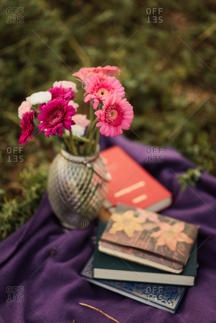 Books and flowers on picnic blanket