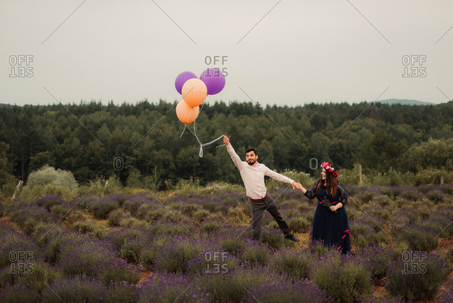 Bridal couple with balloons in field