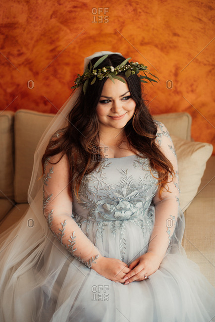 Bride in leafy crown sitting on couch