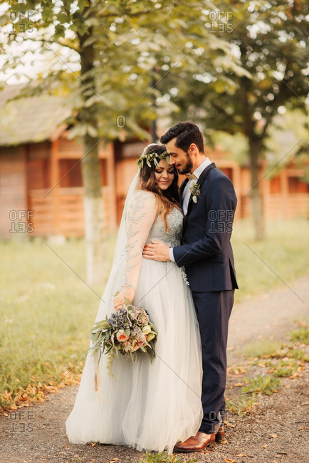 Bride and groom by rural cabins