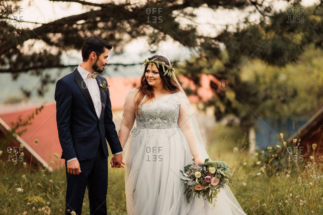 Smiling bridal couple in summer field