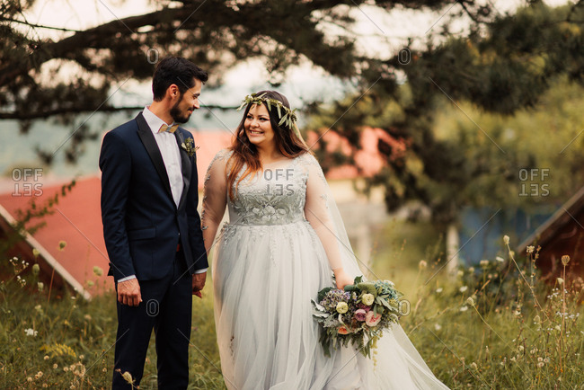 Smiling bridal couple in a summer field