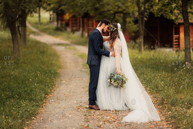 Bridal couple about to kiss on dirt road